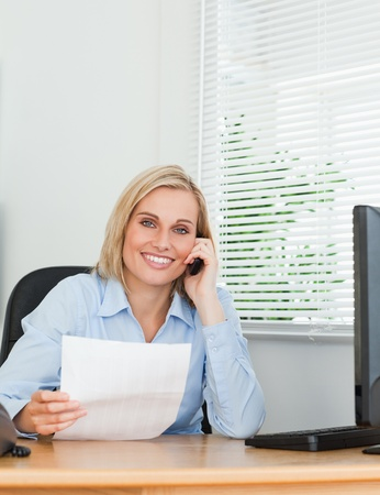 Portrait of a businesswoman looking up from a letter into camera while phoning in her office photo