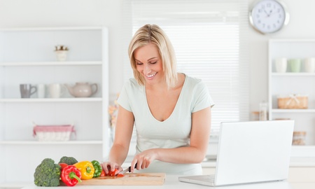 Young woman cutting peppers in the kitchen Stock Photo - 11199269
