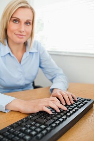 looking into camera: Digitando donna, guardando la telecamera nel suo ufficio