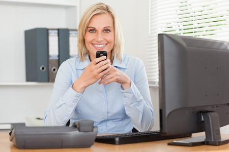 looking into camera: Smiling businesswoman con il cellulare guardando la telecamera nel suo ufficio