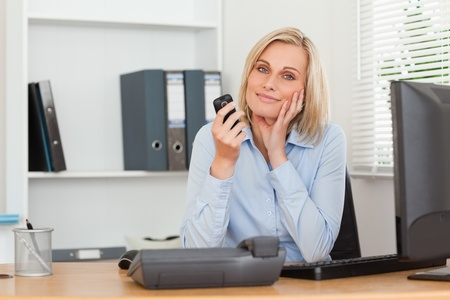 Smiling blondebusinesswoman with mobile looking into camera in her office photo