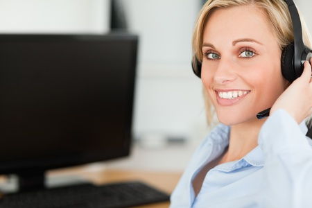 computer help: Portrait of a smiling blonde businesswoman with headset working with computer looking into camera in her office Stock Photo