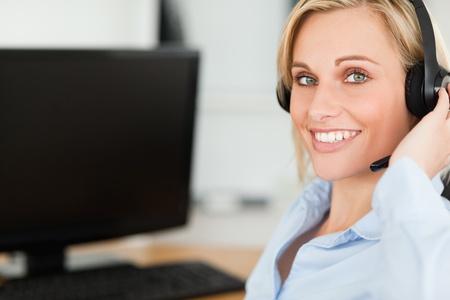 looking into camera: Ritratto di una donna d'affari bionda sorridente con cuffia di lavoro con il computer guardando la telecamera nel suo ufficio