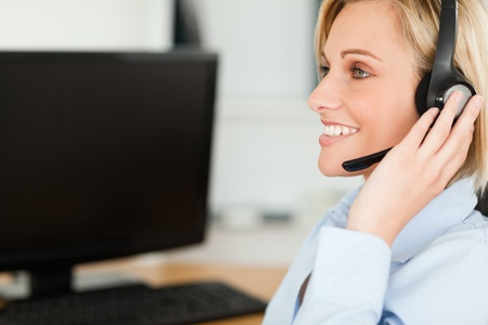 Portrait of a smiling blonde businesswoman with headset working with computer looking elsewhere in her office photo
