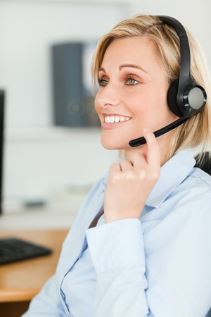 Portrait of a smiling businesswoman with headset looking elsewhere in her office photo