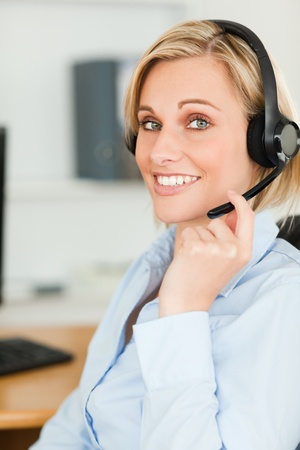 Portrait of a smiling businesswoman with headset lookinginto camera in her office photo