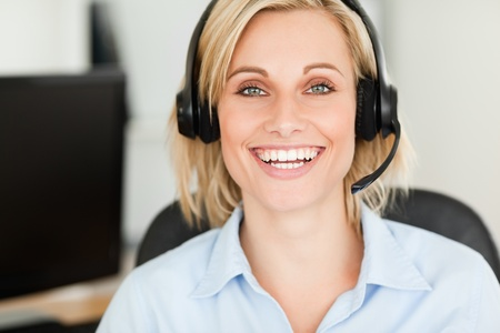 Close up of a blonde woman wearing headset looking into camera in her office photo