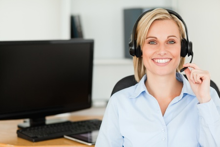 Close up of a blonde smiling woman wearing headset looking into camera in her office photo
