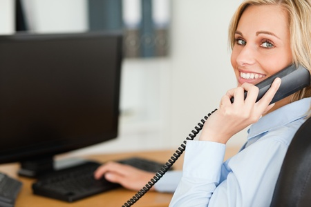 lady on phone: Young blonde businesswoman smiling into camera while on the phone in her office