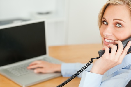 Young businesswoman smiling into camera while on the phone in her office photo