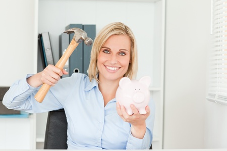 Expectantly woman wanting to destroy her piggy bank in her office photo