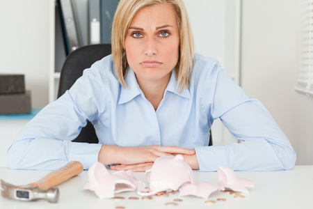 expected: Sad woman sitting in her office in front of an shattered piggy bank with less in than expected Stock Photo