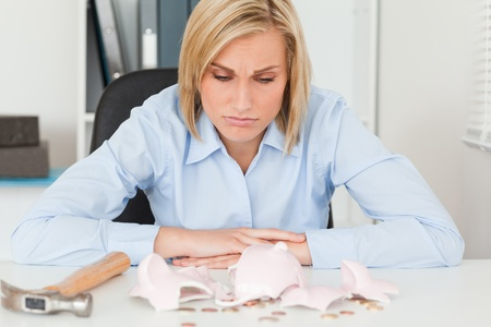 expected: Sulking woman sitting inher office in front of an shattered piggy bank with less in than expected