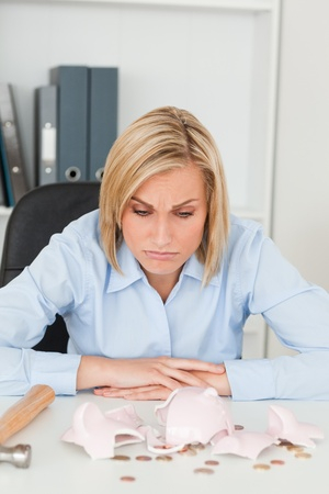 avarice: Sulking woman sitting in front of an shattered piggy bank in her office