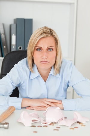 Sulking woman sitting in front of an shattered piggy bank looking into camera in her office photo