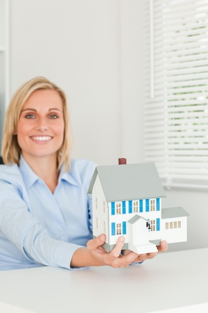 Smiling businesswoman showing model house looking into the camera in her office photo