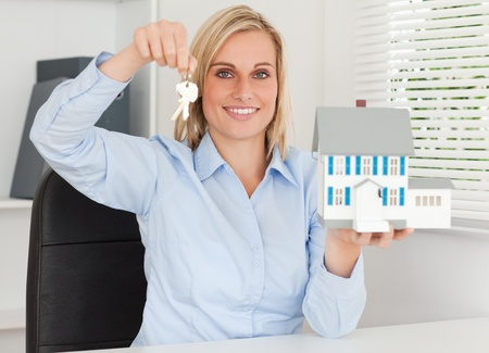 Gorgeous businesswoman presenting model house and keys looking  into the camera in her office photo