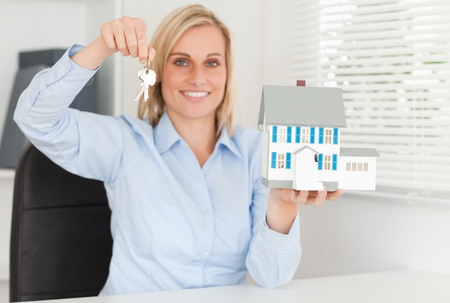 Gorgeous blonde businesswoman presenting model house and keys looking into the camera in her office photo