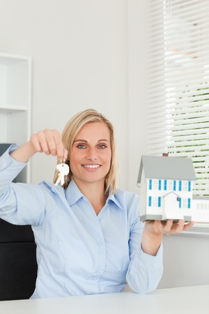 Gorgeous blonde businesswoman showing model house and keys looking into the camera photo