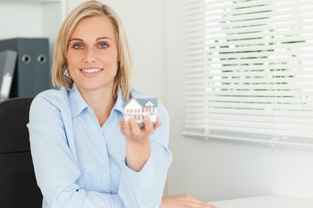 Gorgeous blonde businesswoman showing miniature house looings into the camera in her office photo