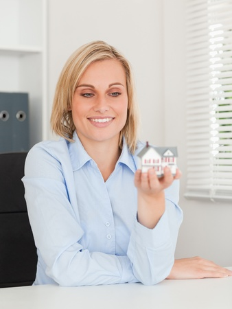 Gorgeous blonde businesswoman showing miniature house looking at it  in her office photo