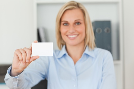 Blonde businesswoman holding a card looking into camera in her office photo