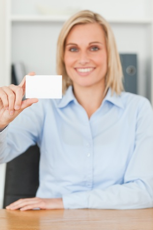 Smiling blonde businesswoman holding a card looks itno camera in her office photo