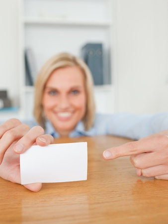 Blonde smiling businesswoman pointing at a card crouching behind her desk in her office photo