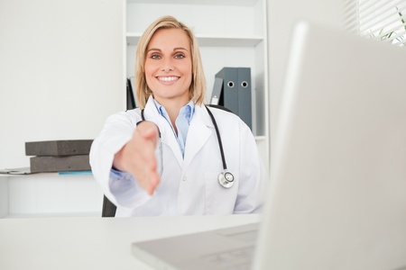 Blonde doctorholding out her hand in her office photo
