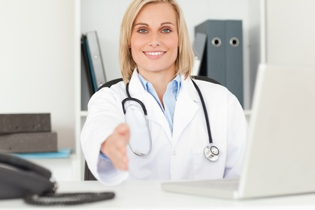 Blonde smiling doctor giving hand in her office photo