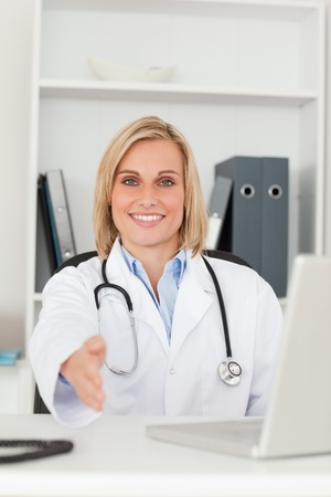 Smiling doctor giving hand in her office photo