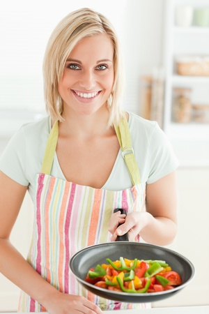 Woman showing a pan with peppers in the kitchen photo