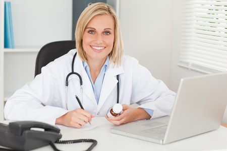 Doctor writing something down holding medicine looks into camera in her office photo