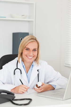 Doctor writing something down while holding medicine looks into camera in her office photo