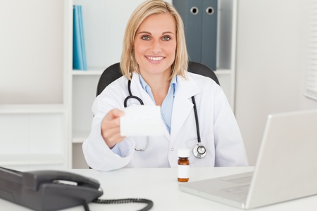Doctor holding prescription in her office photo