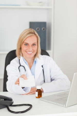 Smiling doctor holding prescription looks into camera in her office photo