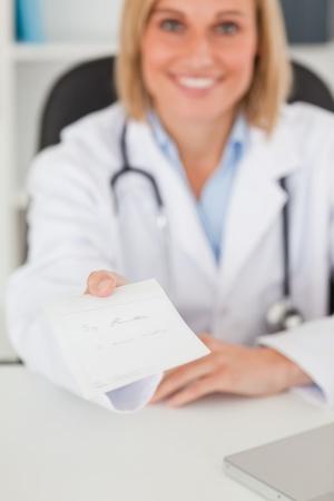 pills in hand: M�dico sonriente rubia dando la prescripci�n se ve en la c�mara en su oficina