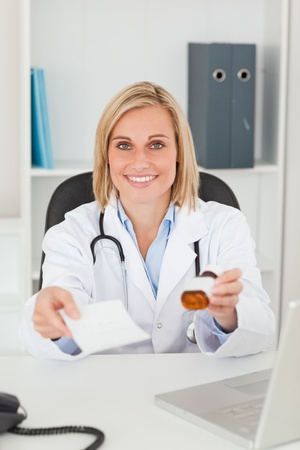 Charming blonde doctor holding prescription and medicine smiles into camera in her office photo