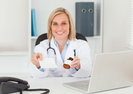 Charming doctor holding prescription and medicine smiles into camera in her office photo