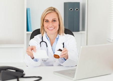 Charming doctor holding prescription and medicine to camera in her office photo