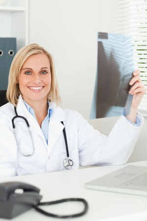 Charming doctor holding x-ray smiles into camera in her office Stock Photo - 11203813