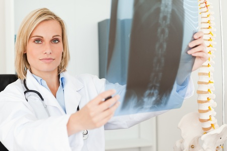 Serious doctor looking at x-ray looks into camera in her office photo
