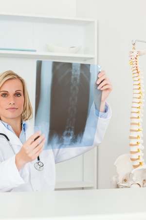 Sad looking doctor holding x-ray looking into camera in her office photo