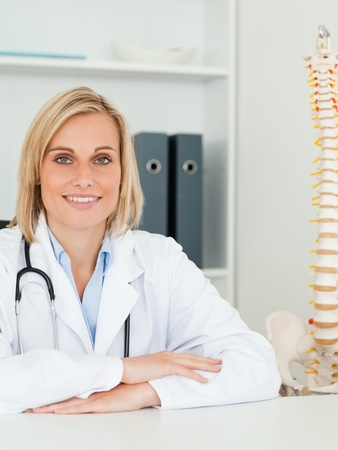Smiling doctor with model spine next to her looks into camera in her office photo