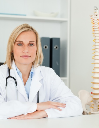 Serious doctor with model spine next to her looks into camera in her office Stock Photo - 11201948