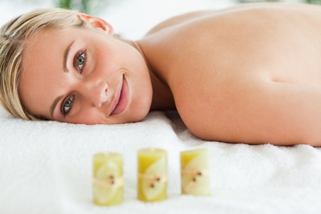 Blonde smiling woman lying on massage lounger in a wellness center photo