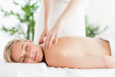woman massage: Gorgeous woman relaxing on a lounger during massage with eyes closed in a wellness center