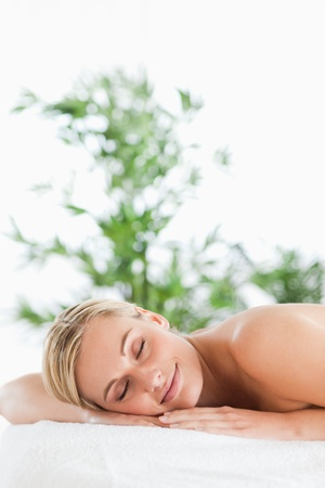 Good looking blonde woman relaxing on a lounger with eyes closed in a wellness center photo