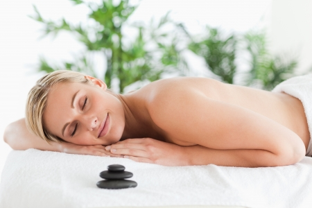 wellness background: Good looking blonde woman lying on a lounger with eyes closed in a wellness center