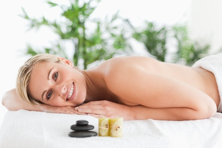 Smiling blonde woman lying on a lounger with stones and candles in a wellness center photo